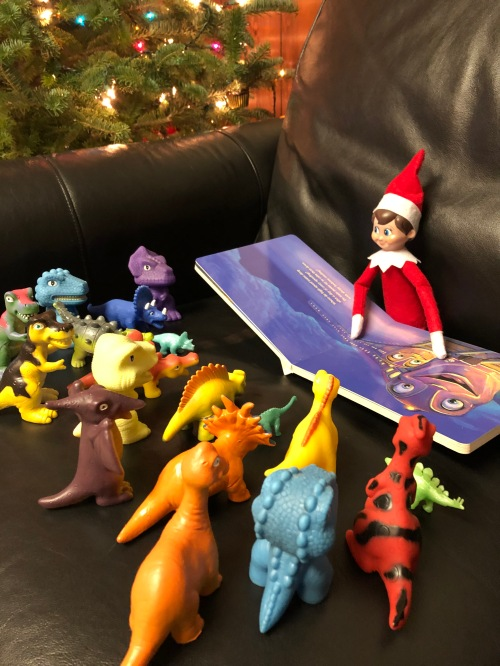 Elf on the Shelf reading to his dino friends
